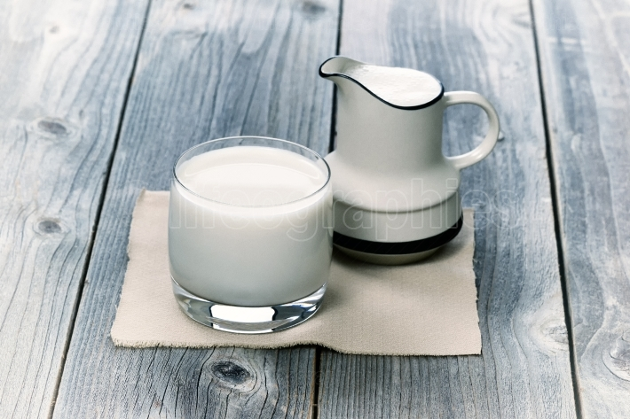 Glass of milk and small pitcher on age wood