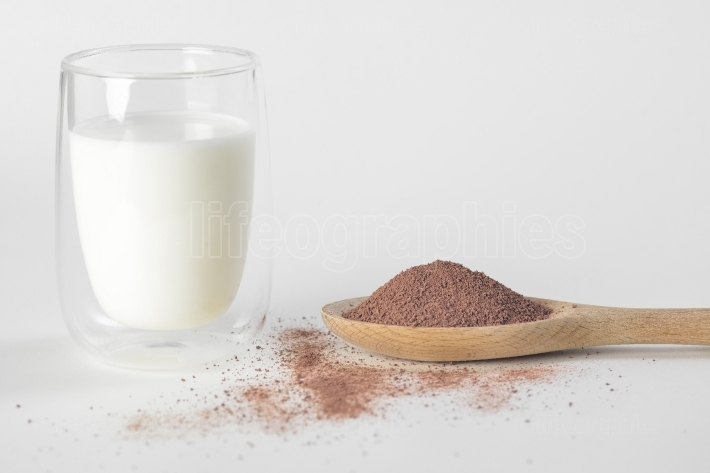Glass of milk with chocolate powder