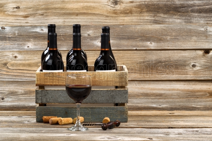 Glass of red wine and full bottles in wood crate on rustic woode