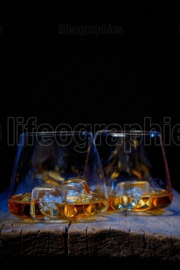 Glass of scotch whiskey and ice isolated