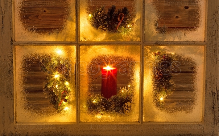 Glowing candle in holiday window