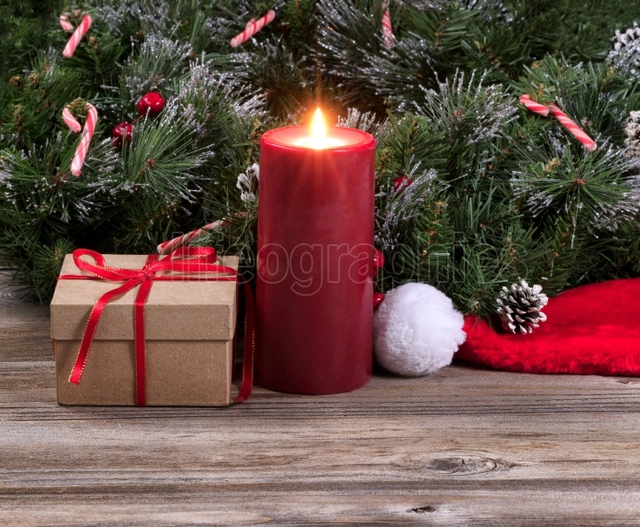 Glowing red candle surrounded by Christmas decoration on rustic