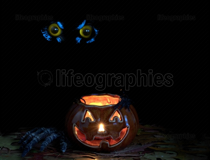 Glowing scary pumpkin decoration in darkness with owl eyes in ba