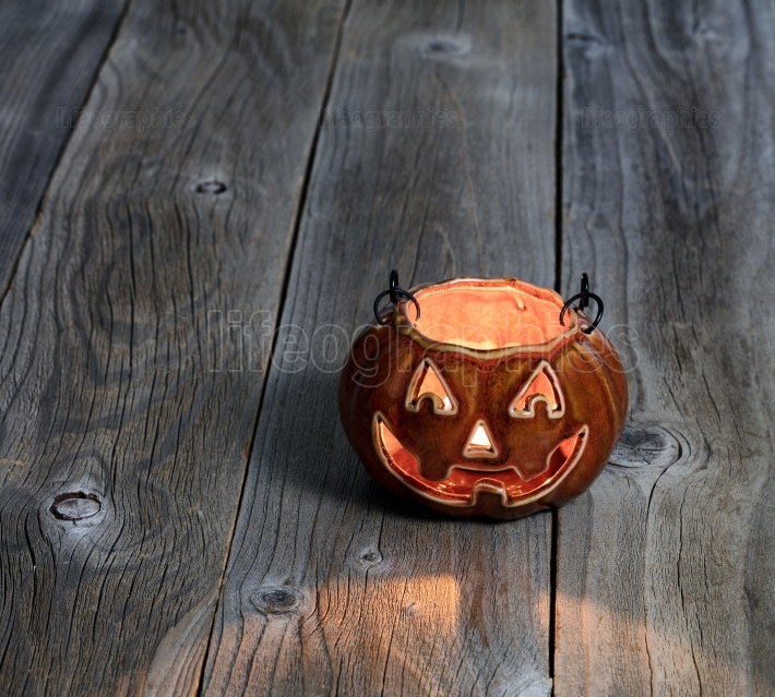 Glowing scary pumpkin decoration on rustic wooden boards