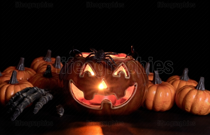 Glowing scary pumpkin decorations and hand in dark background