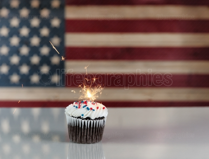 Glowing sparkler inside cupcake with rustic wooden flag of Unite