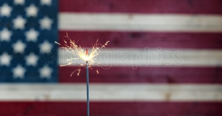 Glowing sparkler with rustic wooden flag of United States of Ame