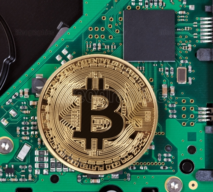 Gold Bitcoin with computer circuit board in background