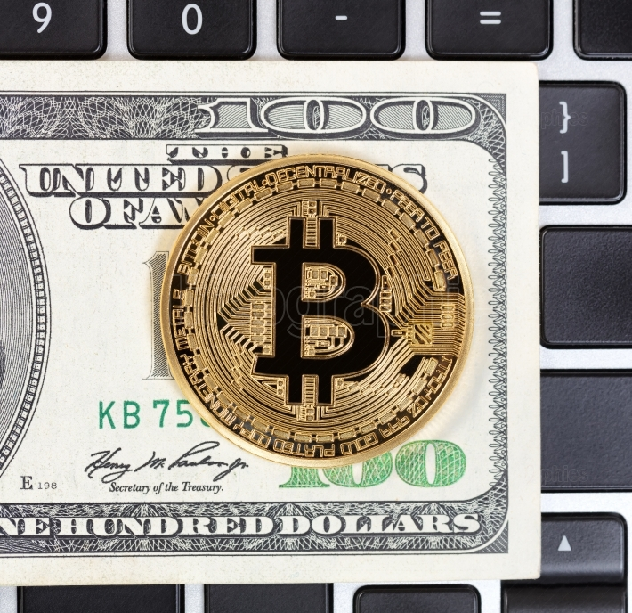 Gold Bitcoin with paper currency and computer keyboard in backgr