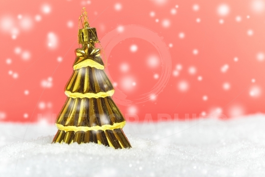 Gold tree ornament with snowy background