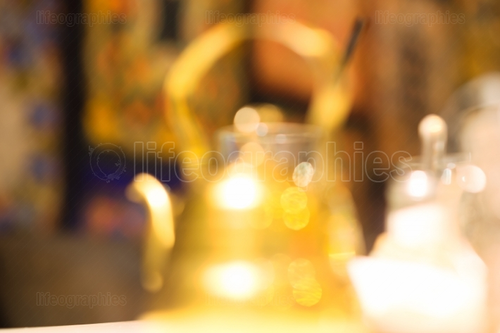 Golden cafe teapot bokeh background
