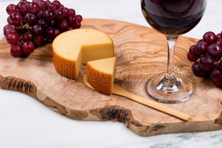 Gourmet cheese plus wine and grapes on wooden server