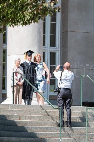 Graduate poses for family photo before college graduation ceremo