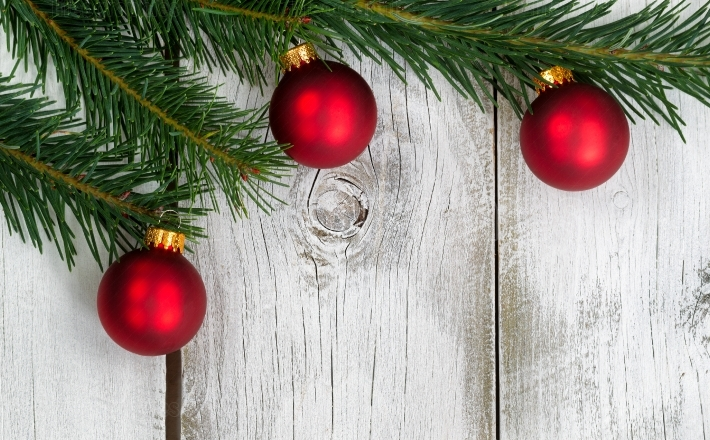 Grand fir branch with three red ornaments on rustic white wooden