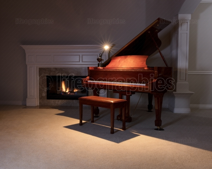 Grand Piano with reading light and glowing fireplace during even