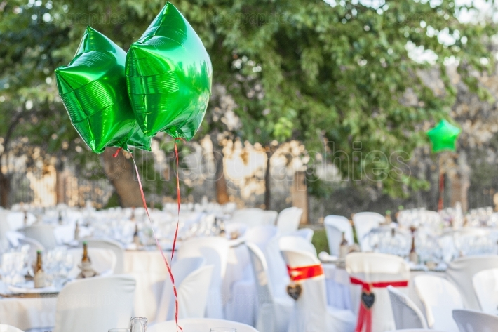 Green shiny balloons at garden table setting for wedding recepti
