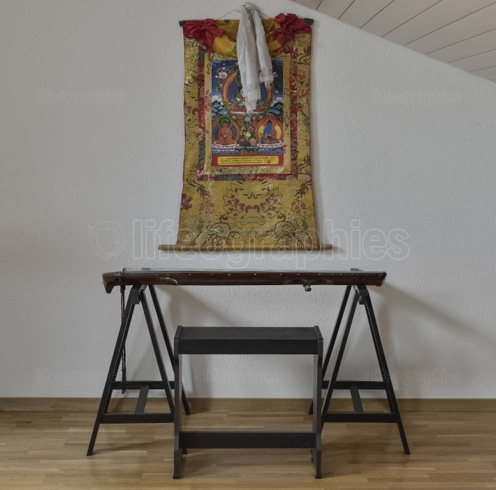 Guqin chinese instrument and tibetan thangka on the wall