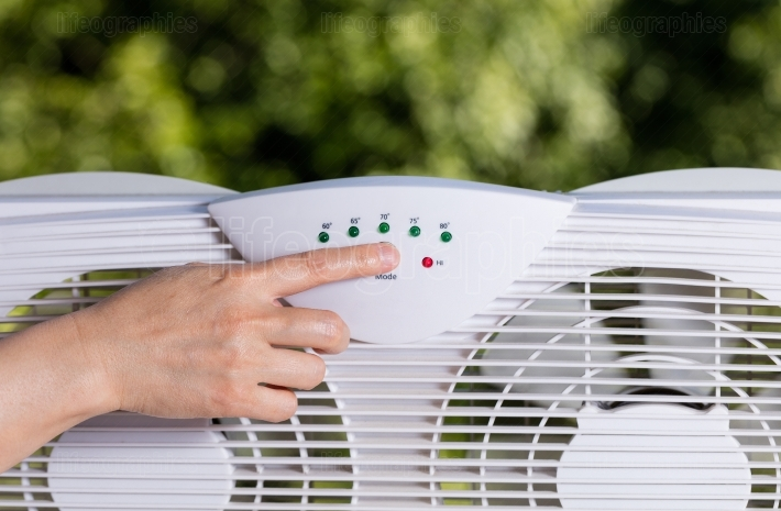 Hand adjusting window fan to cool down room in home during hot w