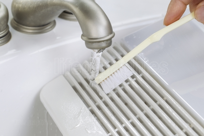 Hand cleaning fan vent cover in sink