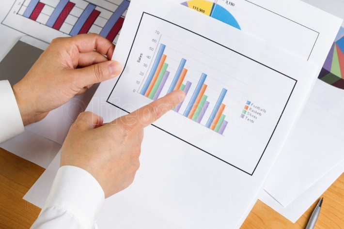 Hand holding bar chart graph while looking at financial data