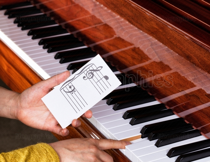 Hand holding music note to play correct key on piano keyboard