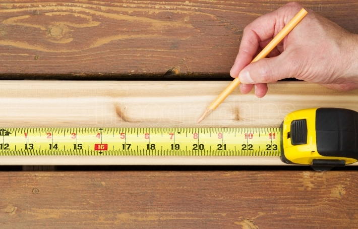Hand measuring wooden board