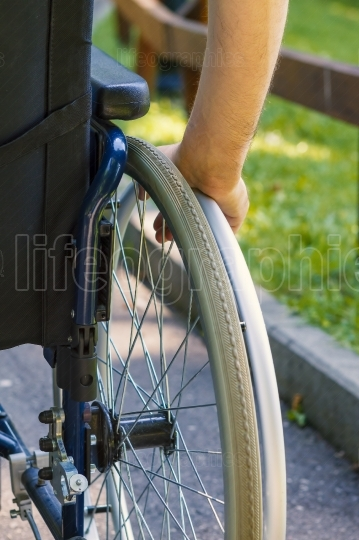Hand of young man on the wheel of wheelchair