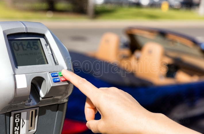 Hand selecting time on parking meter with convertible car in bac
