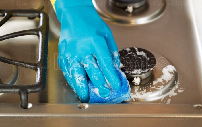 Hand wearing rubber glove while cleaning stove top range with s