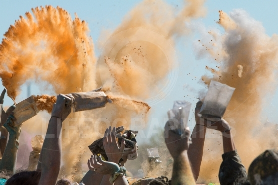 Hands Throw Packets Of Colored Corn Starch At Color Run