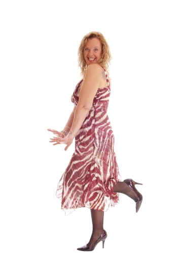 Happy blond woman dancing in dress.