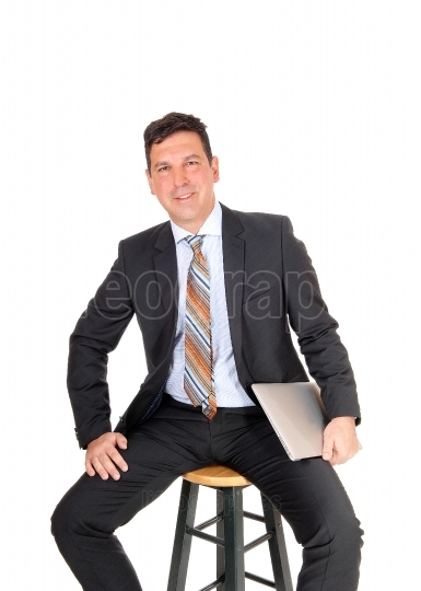 Happy businessman sitting with his laptop