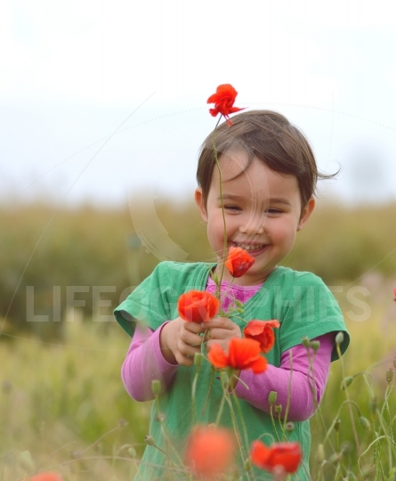 Happy cute child girl on poppies field. Happy children.