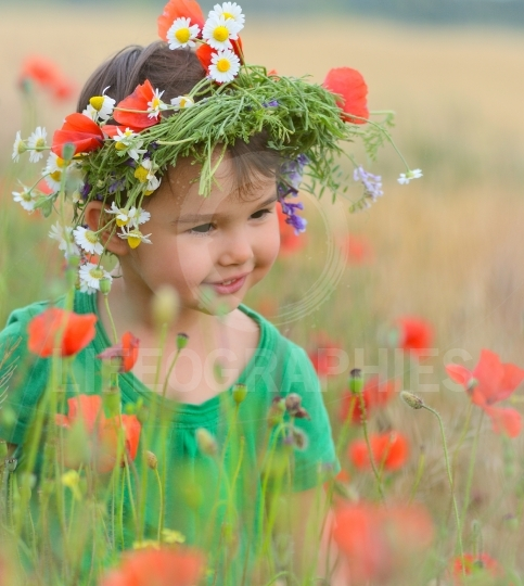Happy cute child girl on poppies field. Happy children. Healthy