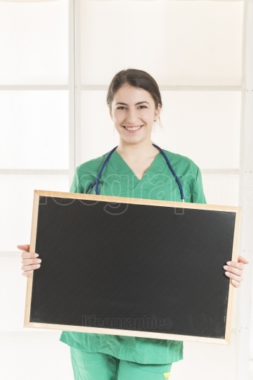 Happy Female Doctor Holding blackboard