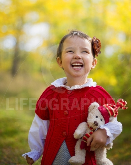Happy girl holding a teddy bear in the  on a sunny autumn day