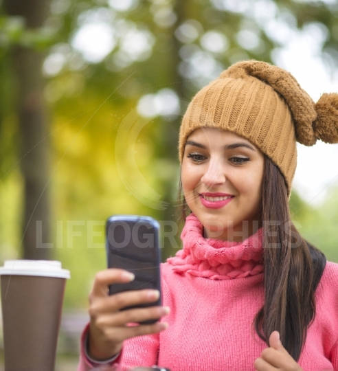 Happy girl taking self picture selfie with smartphone camera outdoors in autumn park on bench