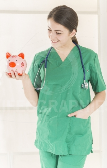 Happy smiling young beautiful female doctor with stethoscope holding pink piggy bank