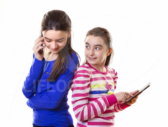 Happy teen girls with digital tablet and smartphone