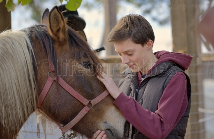 Happy teenager boy with horse