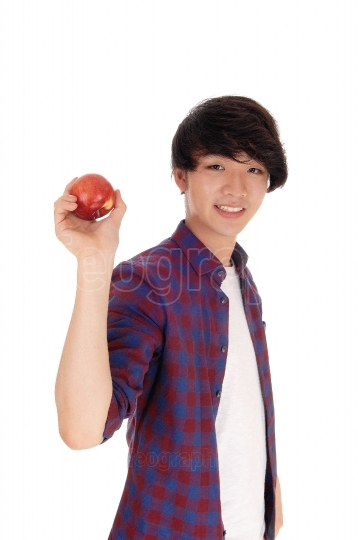 Happy teenager holding red apple