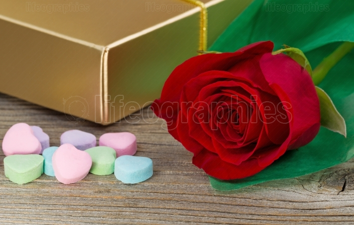 Happy Valentines day with red rose and gifts on rustic wood