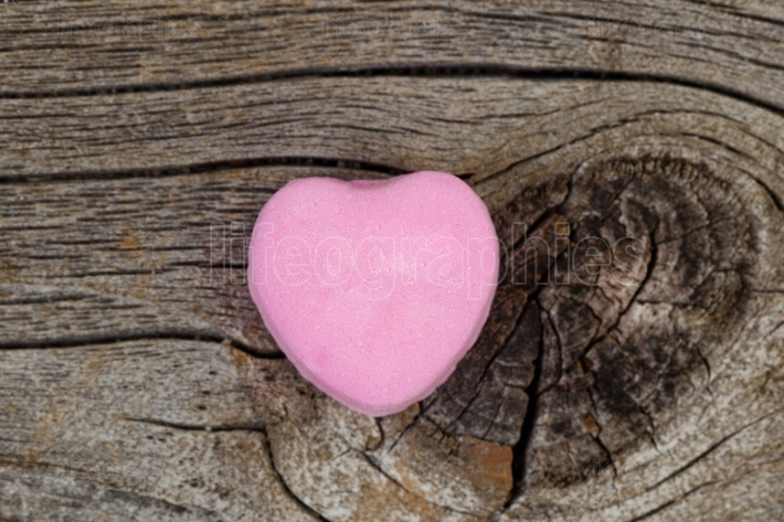 Happy Valentines day with single pink heart shaped candy on rust