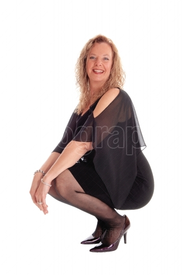 Happy woman crouching on floor.