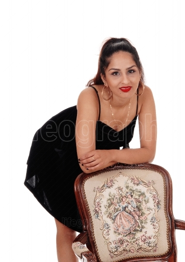 Happy woman leaning on old armchair