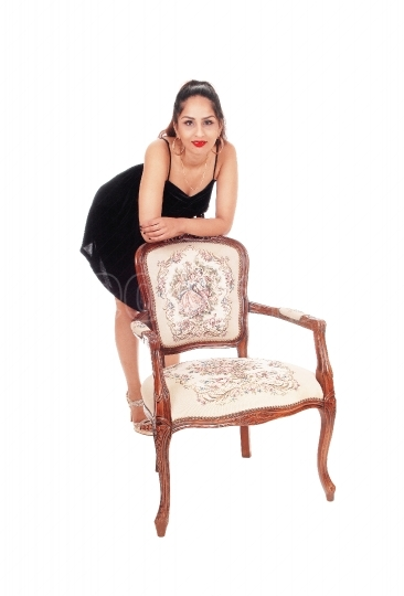 Happy woman leaning over old armchair