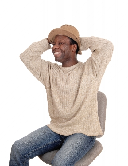 Happy young African man sitting with hat