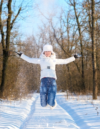 Happy young woman plays with a snow and jumps
