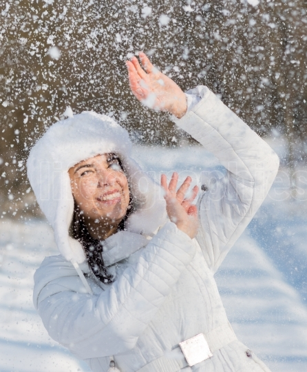 Happy young woman plays with snow