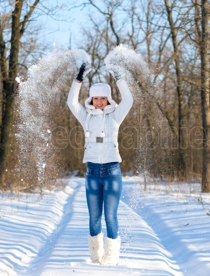 Happy young woman plays with snow and jumps
